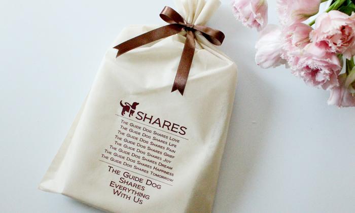 盲導犬のイラストがプリントされたベージュの袋にブラウンのリボンでラッピングした写真