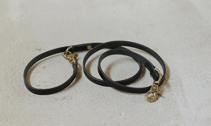 黒の革のリードが巻いて置かれている。首輪につける方と、持ち手部分にもナスカン有。部品はゴールド