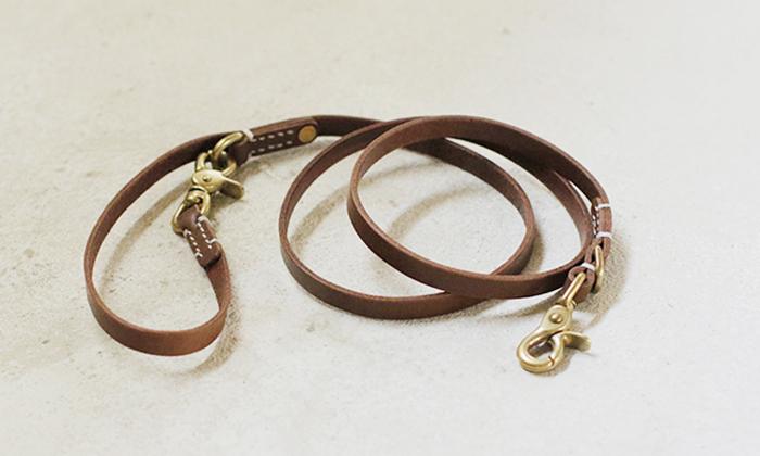 濃い茶色の革のリードが巻いて置かれている。首輪につける方と、持ち手部分にもナスカン有。部品はゴールド