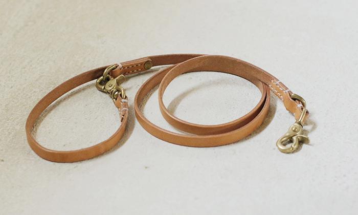 ナチュラルカラー、クリーム色の革のリードが巻いて置かれている。首輪につける方と、持ち手部分にもナスカン有。部品はゴールド