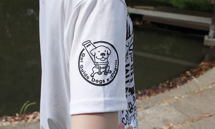右袖アップ。白のTシャツに黒のプリント。丸の中に盲導犬が描かれている。
