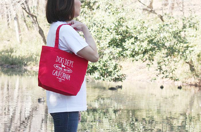 白いTシャツを着た女性が赤いトートバッグを肩からかけている写真。
