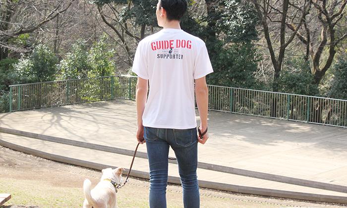男性モデルが犬と散歩する写真