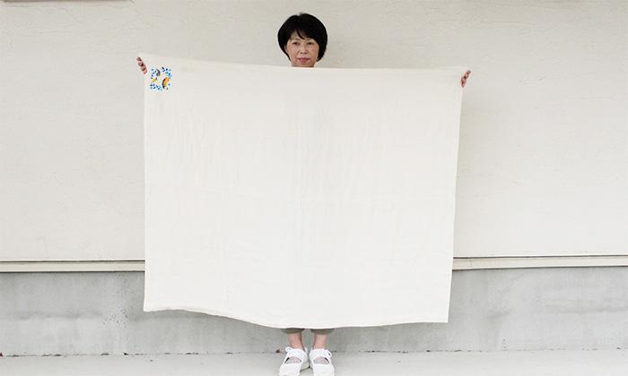 女性がガーゼケットを広げて持つ写真