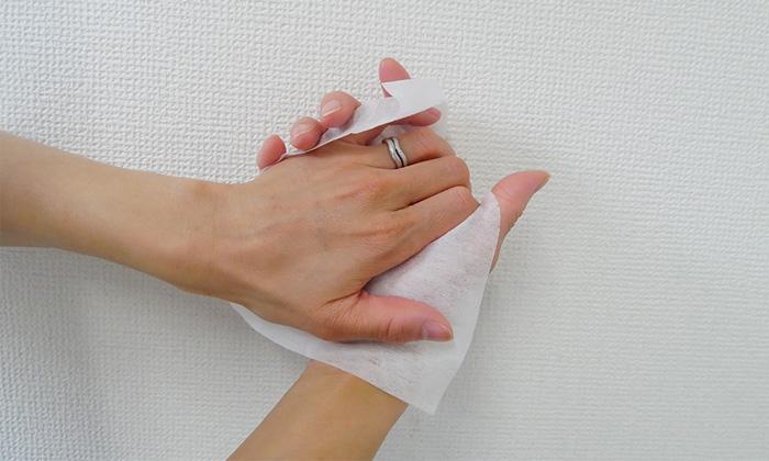 除菌シートで手を拭いている