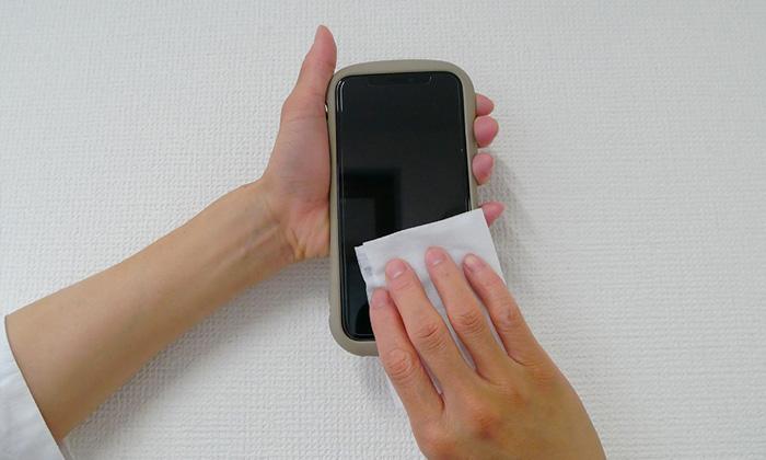 除菌シートでスマホを拭いている。