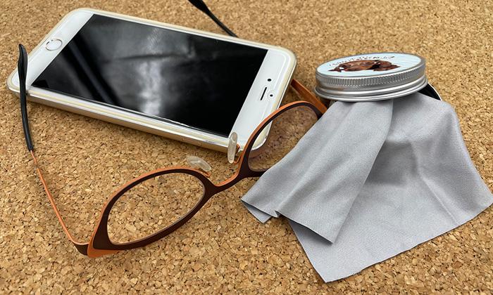 左側にスマホとメガネが置かれている。右側には缶からレンズ拭きが出た状態で置かれている。