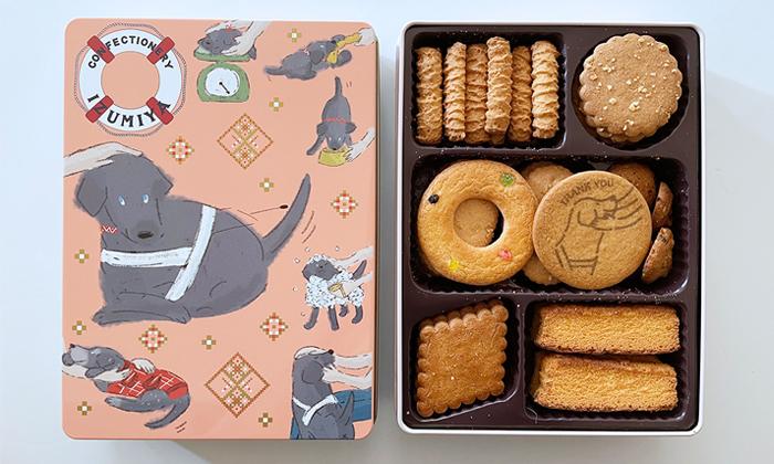 缶の蓋とクッキー缶の中身。デザインは黒ラブの盲導犬ライフを描いている。