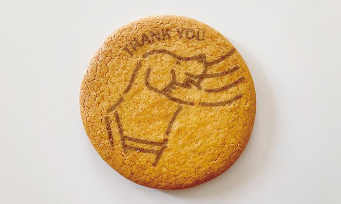 プリントクッキーの写真。ユーザーに両手で頬を撫でられ。喜んでいる盲導犬。上にはTHANK YOUの文字。