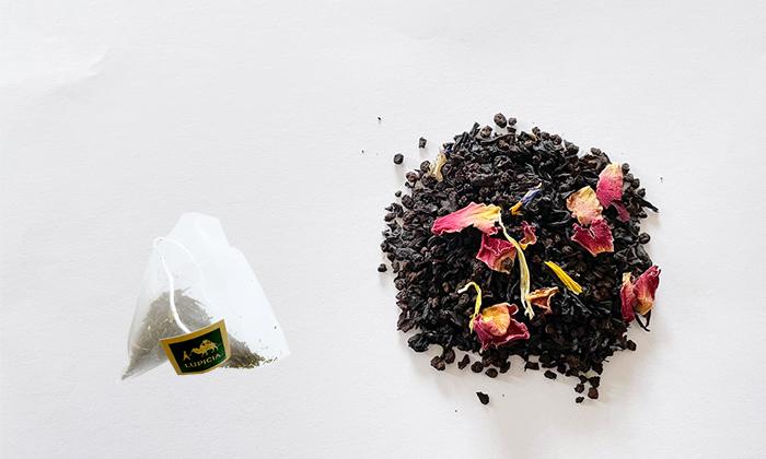 左にティーバック。右に紅茶の茶葉が広げられている。茶葉はローズレッドやマリーゴールド。コーンフラワーといった花びらで彩られている。