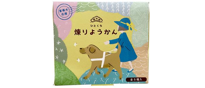 羊羹の箱のイメージ。デザインは。中央に青い帽子とワンピースを着た女の子が盲導犬と一緒に歩いている。その周りには。緑だけでなくピンクや青の色とりどりな山が連なっている。