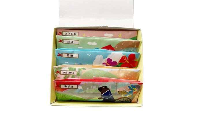 羊羹の箱の中身の写真。手前から。あずき。小倉白小豆。黒糖。抹茶。ほうじ茶の順に羊羹が並んでいる。